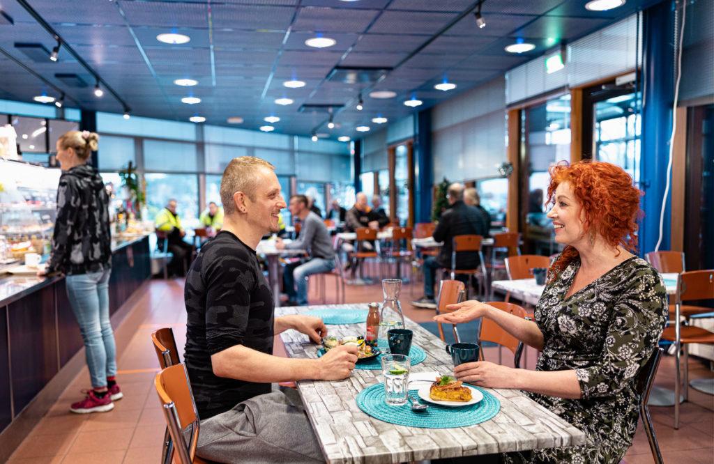 Mies ja nainen keskustelevat iloisesti tarjottavien äärellä Cafe Kristinan sisäpuolella.